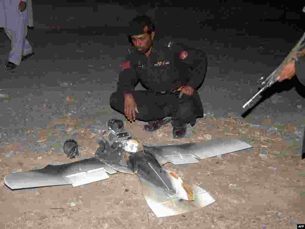 Pakistani security personnel examine a crashed U.S. surveillance drone some 2 kilometers inside Pakistani territory in the town of Chaman on August 25. Photo byAsghar Achakzai for AFP