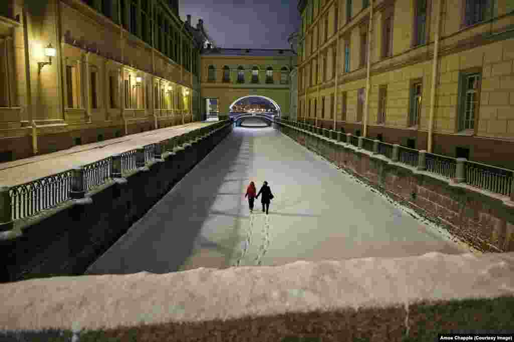 "A couple walking on the frozen Winter Canal in the city center. Petrosyan said this picture came at the end of a long, unsuccesful night shooting a snowstorm. He was on his way home when the couple walked out from a bridge beneath him. Petrosyan remembers the moment as ""unexpected and beautiful, like a dream."""