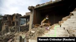 Зілзаладан құлаған үйінің орнында отырған әйел. Непал, 2 мамыр 2015 жыл.