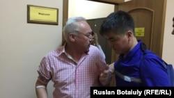 Председатель Союза журналистов Казахстана Сейтказы Матаев (слева) выходит из медпункта в суде. Астана, 23 августа 2016 года.