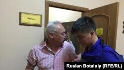 Сейтказы Матаев покидает зал суда с врачом скорой помощи.
