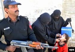 Офицер полиции охраняет врачей, делающих прививки от полиомиелита. Кветта, декабрь 2014 года