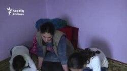 Soyuqda yerdə oturub dərslərini hazırlayan uşaqlar