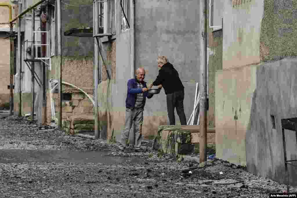 Женщина делится едой с соседом у разрушенного многоквартирного дома в Степанакерте. 8 октября 2020 года.