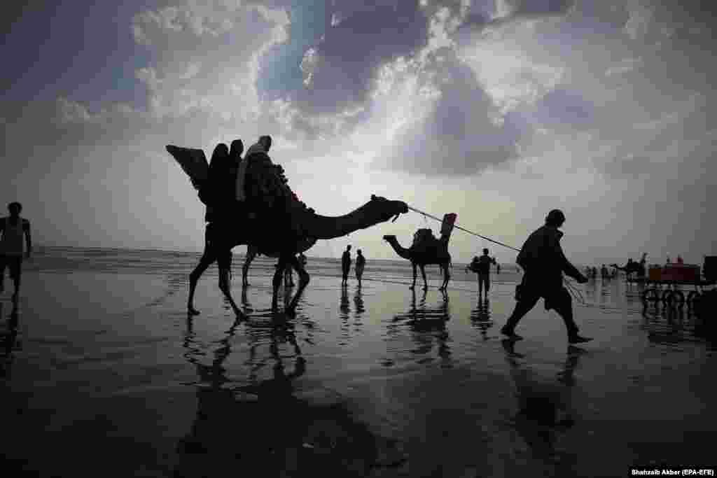 Людзі зьбіраюцца на пляжы. Гарачае надвор'е ў Карачы, Пакістан, 14 верасьня.