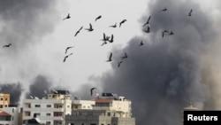 Fotografi në të cilën shihen zogjtë duke fluturuar derisa tymi ngritet nga ajo që është përshkruar si sulm izraelit ajror kundër Rripit të Gazës më 21 nëntor