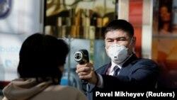 Сотрудник в защитной маске проверяет температуру тела посетителя у входа в торговый центр. Алматы, 17 марта 2020 года.
