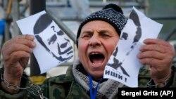 Un demonstrant la Kieva cu portretul lui Viktor Ianukovici în 2013