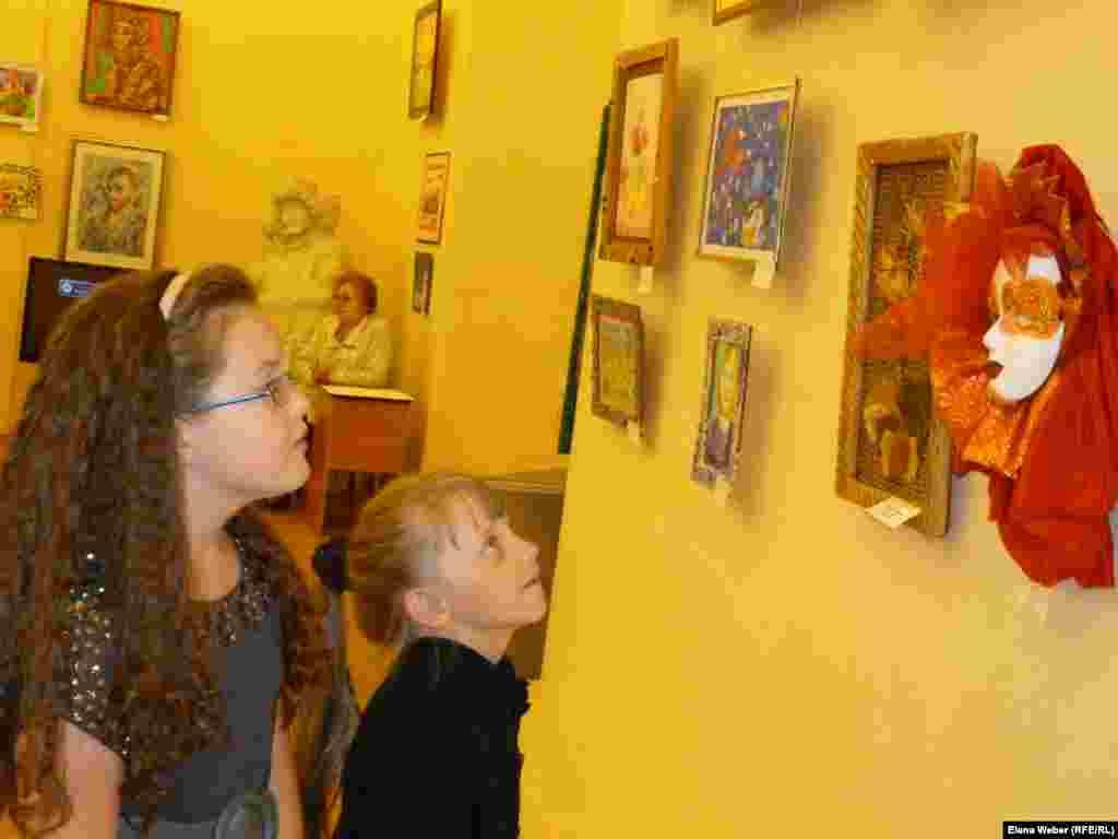 Участницы выставки разглядывают работы других участников.