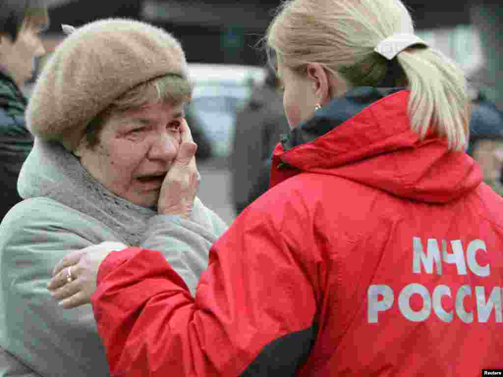 A woman cries while standing next to an Emergencies Ministry official near Park Kultury metro station.