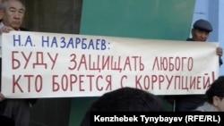 Президент Назарбаевтың сөзі жазылған плакат ұстаған белсенділер Алматы қалалық сотының алдында наразылық акциясында тұр. 17 қыркүйек 2013 жыл.