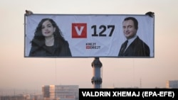 Workers in the Kosovar capital, Pristina, install a giant election poster showing prime ministerial candidate Albin Kurti (right) and acting President Vjosa Osmani.