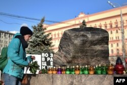 A woman places a candle and flowers at the memorial to the victims of Soviet-era political repression in Moscow. New polls show that 50 percent of Russians believe they may see similar political repressions again in their lifetime.