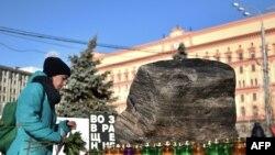 Женщина несет свечи и цветы к Соловецкому камню на Лубянской площади в Москве, 29 октября 2014