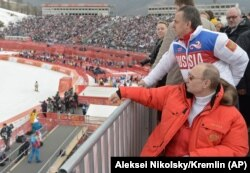 Russian President Vladimir Putin (foreground) and then-Sports Minister Vitaly Mutko (top) in Sochi in 2014