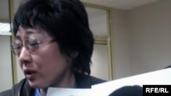 Экологтар сотында арандату мен қастандық турасында мәлімдеме жасаған белгісіз әйел баласының суретін ұстап тұр. Астана, 28 қыркүйек, 2009 жыл.