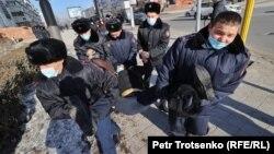 Полицейские тащат задержанного во время несогласованной с властями протестной акции. Алматы, 10 января 2021 года.