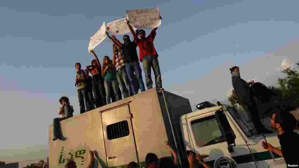 Georgian students stand on a prison-transfer vehicle during a protest in Tbilisi. (Reuters/David Mdzinarishvili)