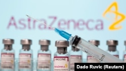 "Vials labeled ""AstraZeneca COVID-19 Coronavirus Vaccine"" and a syringe are seen in front of a displayed AstraZeneca logo, March 10, 2021."
