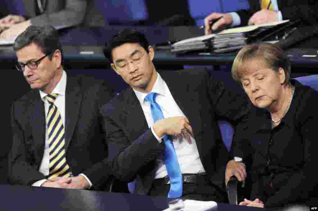 16 декабря 2011 года канцлер Германии Ангела Меркель (справа), министр экономики Филипп Реслер (в центре) и бывший министр иностранных дел Гидо Вестервелле (слева) вместе закрыли глаза на заседании в Бундестаге.