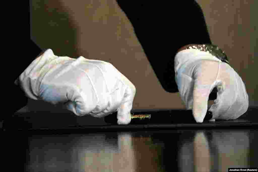 Түндүк Кореянын лидеринин жардамчысы ручканы столго коюп жатат, аны АКШ президенти менен кол коюла турган аземге чейин дыкат сүртүп тазалашкан.