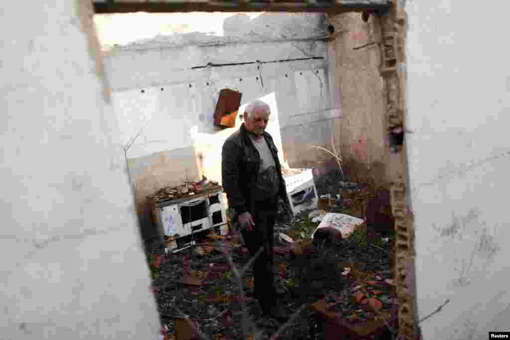Sava Knezevic, 65, walks through his house in the Croatian town of Knin, destroyed during the Balkan wars of the early 1990s.