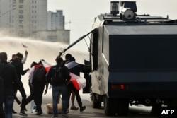 Протестующие разбирают водомет 4 октября во время акции за освобождение политзаключенных в Минске