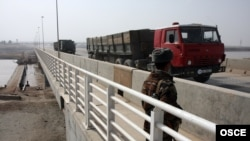 Trucks cross a bridge over the Piandj River on the Tajik-Afghan border.