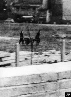 Восточногерманские пограничники уносят человека, по которому был открыт огонь при попытке бежать 4 сентября 1962 года.