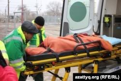 Дәрігерлер талып қалған оқушыны жедел жәрдем көлігіне салып жатыр. Батыс Қазақстан облысы, 4 желтоқсан 2014 жыл.