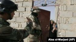 Иракта рейд учурунда аскерлер үйлөрдү кыдырып жүрөт.