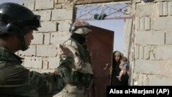 Наджаф қаласы маңындағы ауылда жергілікті тұрғынмен сөйлесіп тұрған сарбаздар. Ирак, 29 мамыр 2018 жыл.