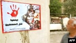 "In Baghdad, a poster reading ""Stop Killing Journalists"" bears photographs of media personnel killed in the line of duty."