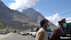 Men wear protective face masks as a preventive measure against coronavirus disease (COVID-19) outbreak as they stand by a queue of vehicles at a check post while entering Gilgit in northern Pakistan on March 22.