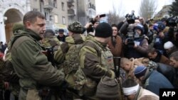 Пленные украинские солдаты стоят на коленях перед лидером самопровозглашенной Донецкой народной республики Александром Захарченко (слева). Донецк, январь 2015 года.