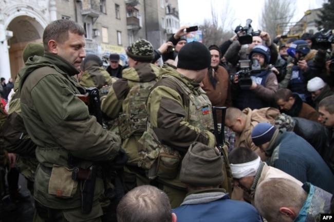 """Глава """"ДНР"""" Захарченко рядом с пленными в Донецке. Пленных солдат провели через город и поставили на колени в том месте, где попал под артобстрел троллейбус, после этого местным разрешили закидать пленных снежками и бутылками"""