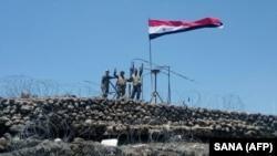 Военнослужащие правительственных сил Сирии у флага Сирии в южной провинции Дераа. Фото агентства SANA, 17 июля 2018 года.