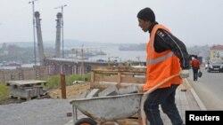 Трудовой мигрант выкладывает плитку на тротуаре. Иллюстративное фото.