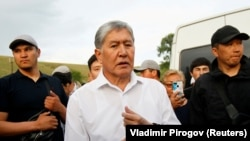 Former Kyrgyz President Almazbek Atambaev and supporters attend a meeting with journalists in the village of Koi-Tash near Bishkek on June 27.