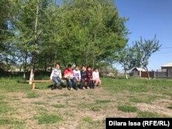 Дети сидят на скамейке во дворе школы в Кызылжаре. 28 апреля 2021 года.