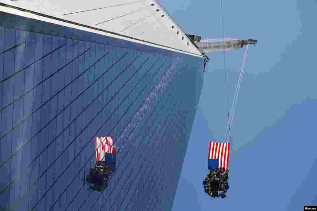 A U.S. flag flies in the wind as the final piece of a spire is lifted to the top of One World Trade Center in New York. (Reuters/Lucas Jackson)