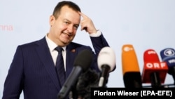 Serbian Foreign Minister Ivica Dacic talks to the media as he arrives for an informal meeting of foreign affairs ministers at the Hofburg Palace in Vienna on August 31.