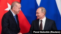 RUSSIA -- Russian President Vladimir Putin and Turkish President Tayyip Erdogan shake hands during a news conference following their talks in Moscow, March 5, 2020