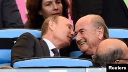 Russian President Vladimir Putin (left) speaks to FIFA President Sepp Blatter during the 2014 World Cup final in Rio de Janeiro.
