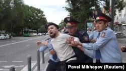 Полицейские задерживают активиста Димаша Альжанова на месте предполагаемой акции протеста в Алматы. 12 июня 2019 года.