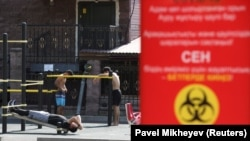 Люди на спортивной площадке вблизи доски с информацией о мерах предосторожности, связанных с пандемией коронавирусной инфекции. Алматы, 12 июля 2020 года.