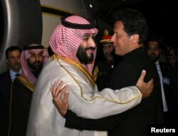 Pakistani Prime Minister Imran Khan (right) greets Saudi Arabia's Crown Prince Mohammed bin Salman on his arrival at Pakistan Air Force (PAF) Nur Khan Base in Rawalpindi on February 17.