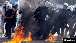 Таксим алаңына келген полицейлерге шерушілер жанғыш сұйықтық құйылған құмыралар лақтырды. Стамбул, 11 маусым 2013 жыл.
