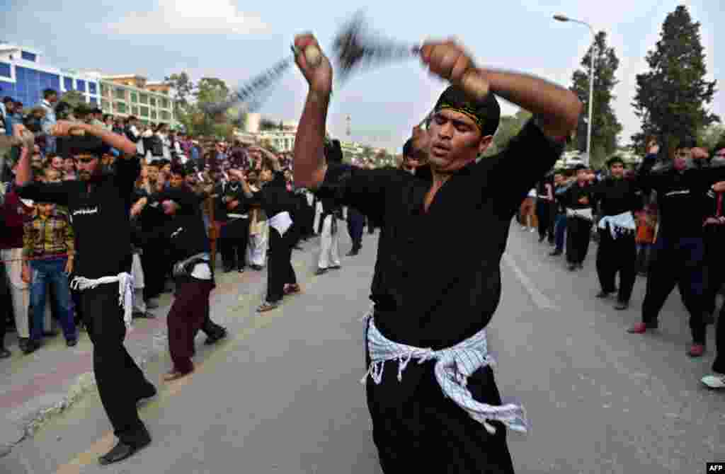 Pakistani Shi'ite Muslims flagellate themselves during a religious procession to mark the Day of Ashura, which commemorates the anniversary of the death of the Prophet Muhammad's grandson Imam Hussain in 680 A.D. (AFP/Farooq Naeem)