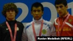 Казахстанский спортсмен Мухамбет Куатбек (в центре) после победы в соревновании борцов-вольников. Нанкин, 27 августа 2014 года.